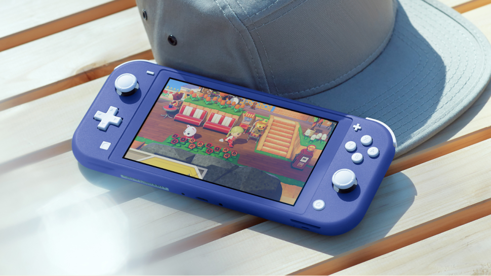 Nintendo Switch Lite in the blue colorway on a table next to a hat