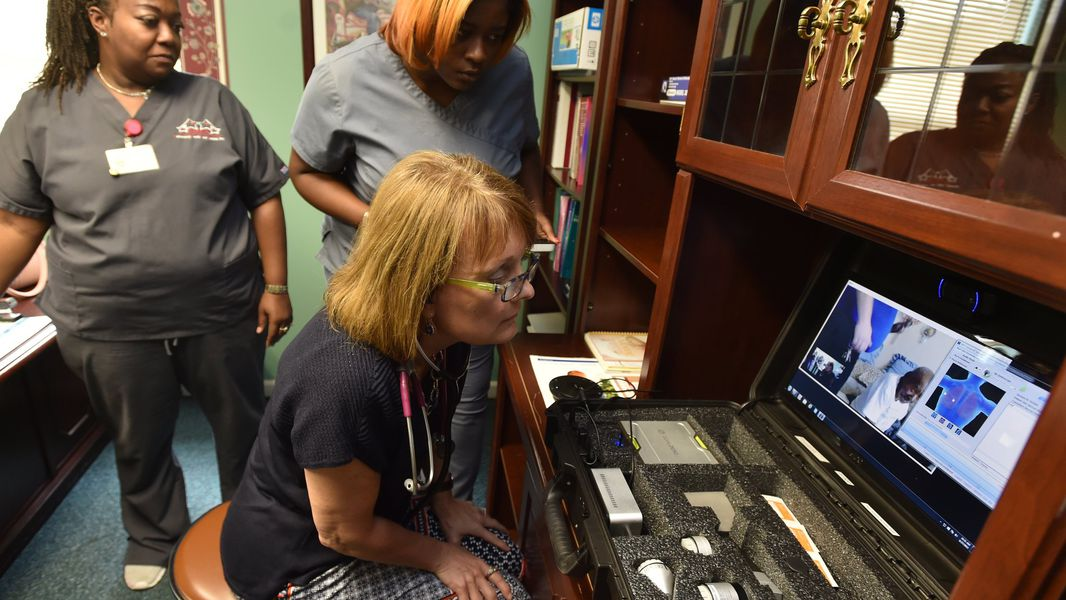 At the Community Health Care Systems center on Hamilton Street in Sparta, Ga., nurse practitioner Kemberly Smith (foreground) and medical assistants Keisha Hill and Joy Robinson examine a patient via telemedicine on Aug. 27, 2015. BRANT SANDERLIN /BSANDERLIN@AJC.COM
