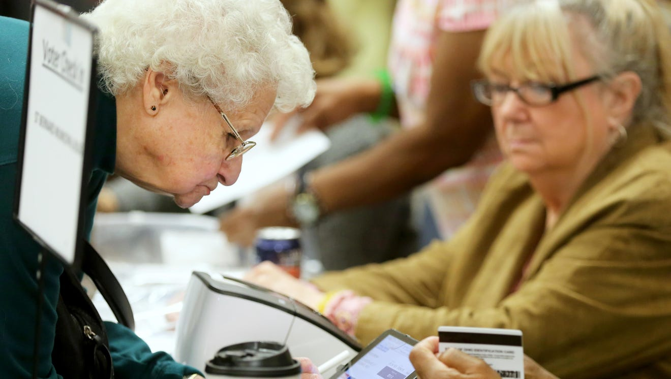 """Rose Brown, 86, of St. Bernard, signs the e-polling book as she checks in to vote. In search of technologically savvy poll workers, the Hamilton County Board of Elections is encouraging local employers to start """"Day Off For Democracy"""" program so employees can serve."""