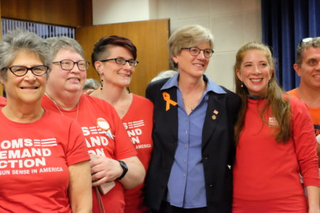 Morey is flanked by gun violence reduction advocates wearing orange shirts that read: Moms demand action for gun sense in America