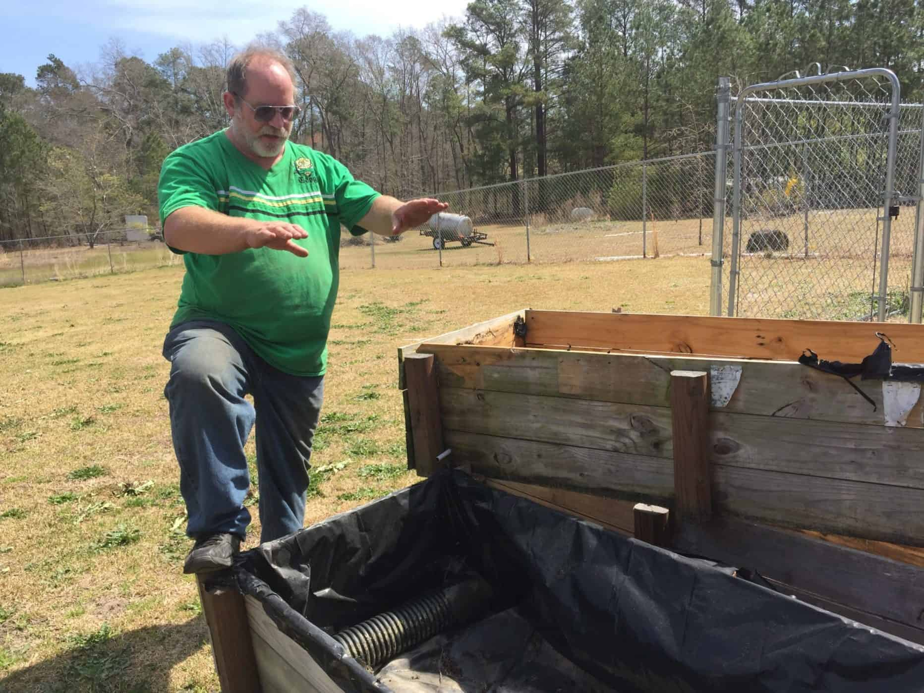shows a neighbor of the Fayetteville DuPont plant standing near garden boxes he proposes to use in an experiment to see how much GenX gets into food grown with contaminated water