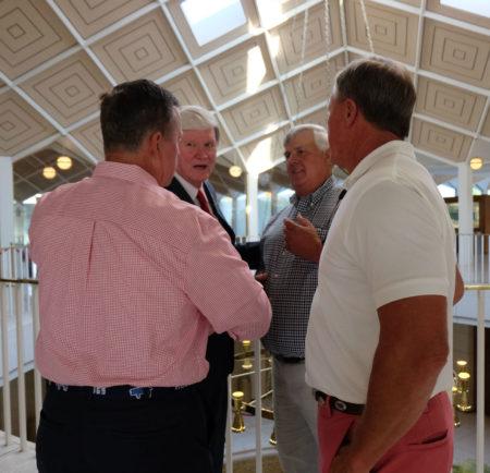 shows four older white men speaking