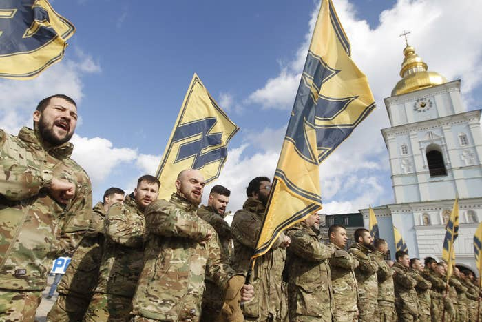 Men in military garb stand with flags featuring the Azov movement's symbol, which is similar to the Wolfsangel, widely used by Nazi German divisions during the Second World War