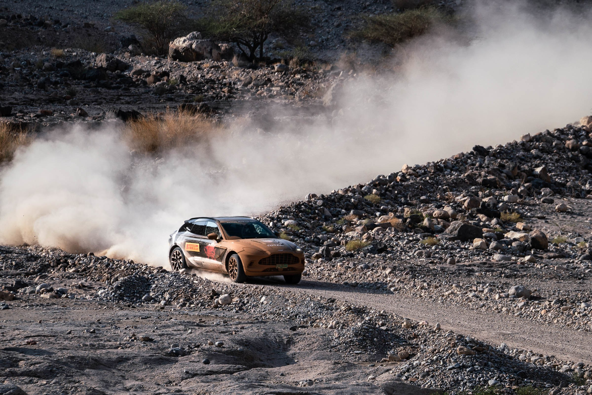 Aston Martin DBX SUV sliding around a curve in Oman