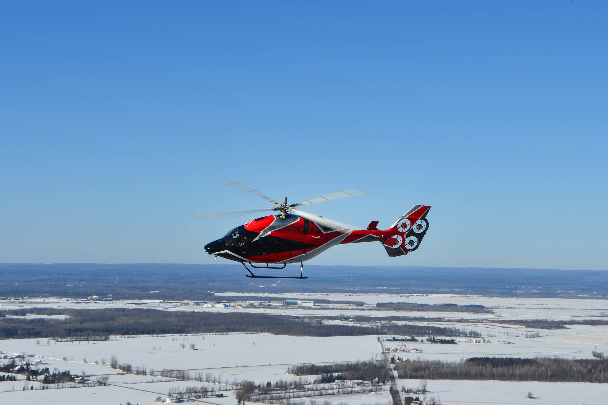 A red helicopter flying over a snowy landscape