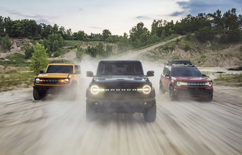 pre production versions of the all new 2021 bronco family of all 4x4 rugged suvs, shown here, include left bronco two door in cyber orange metallic tri coat, bronco four door in shadow black and bronco sport in rapid red metallic tinted clearcoat