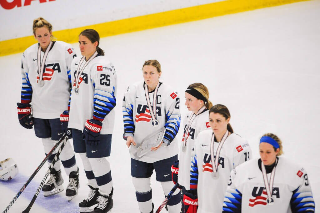 CALGARY, AB - AUGUST 31: Team United States stands dejected on the blueline as team Canada receives their goal medals in the 2021 IIHF Women's World Championship gold medal game played at WinSport Arena on August 31, 2021 in Calgary, Canada. Canada defeated United States 3-2 in overtime. (Photo by Derek Leung/Getty Images)