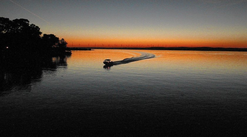 Boat carving a wake in delta waters reflecting orange sunset