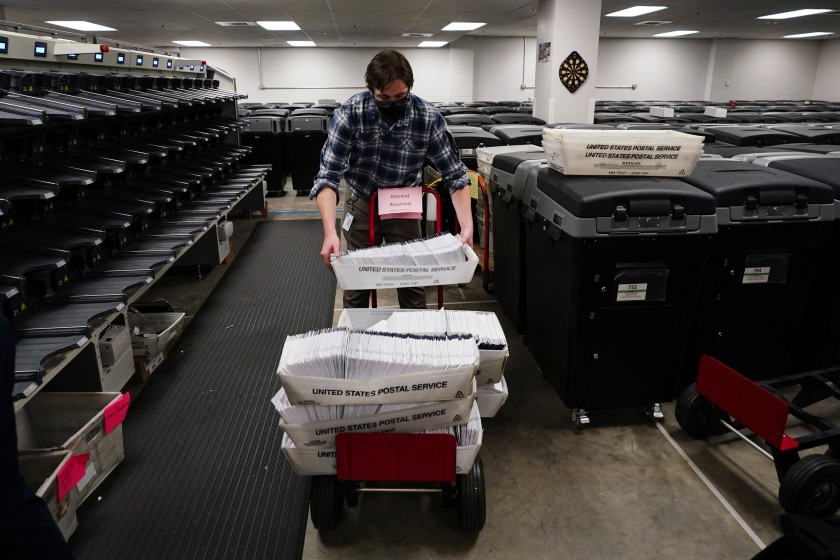 An elections worker in Chester County, Pa., stacks bins of mail-in ballots last week.