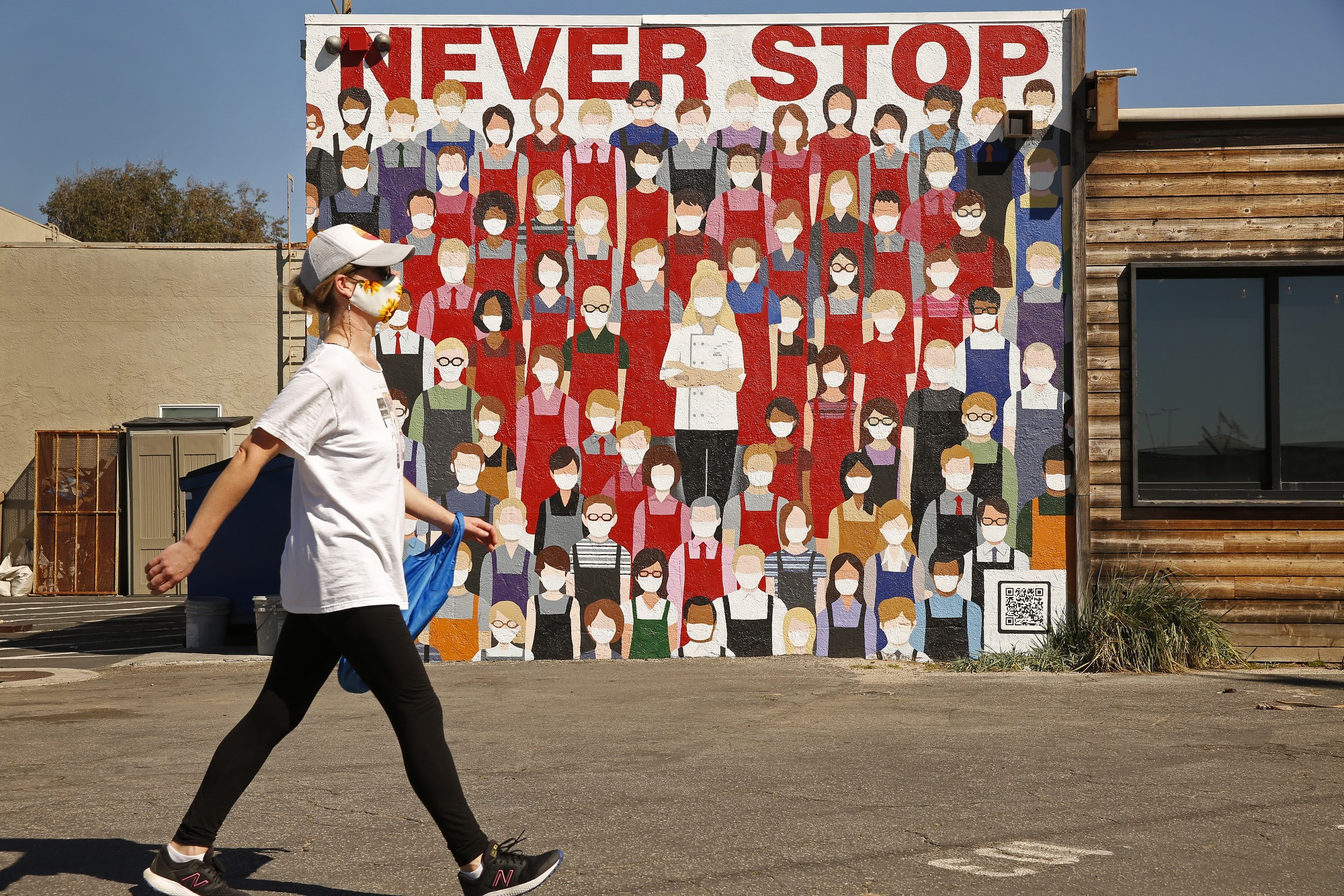 A woman walks past a mural of a crowd of people in masks