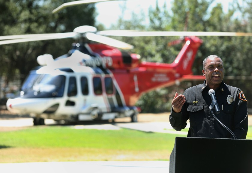 Los Angeles County Fire Chief Daryl Osby speaks with a helicopter as a backdrop