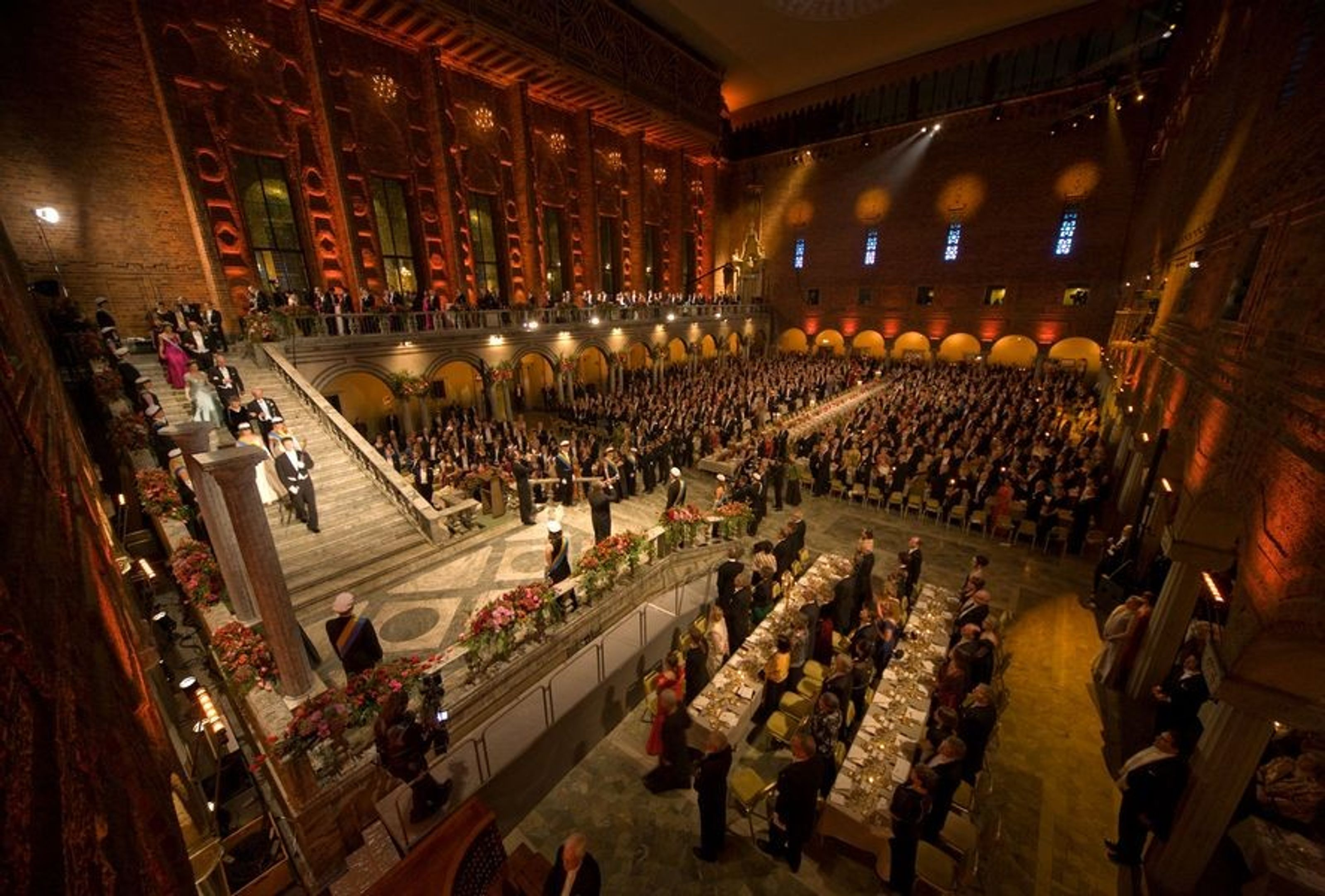 Sweden's King Carl Gustav and Queen Silvia arrive at the Stadshuset's cavernous Blue Hall for the Nobel Banquet